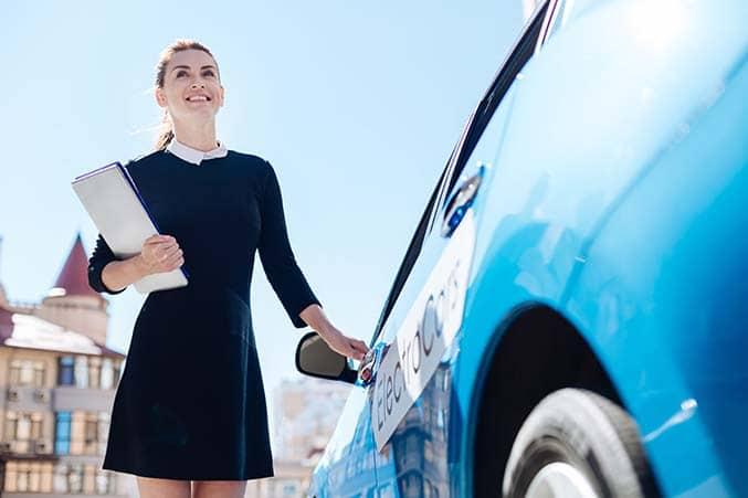 Femme d'affaire rechargeant sa voiture électrique