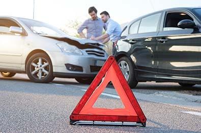 Deux hommes remplissant un constat suite à un accident de voiture