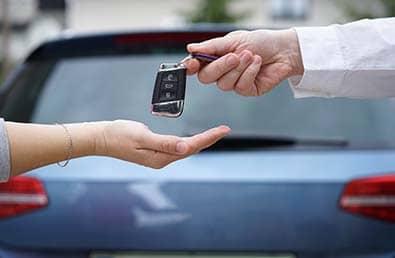 Un vendeur de voiture donne à son client les clés d'une voiture avec une voiture en arrière-plan