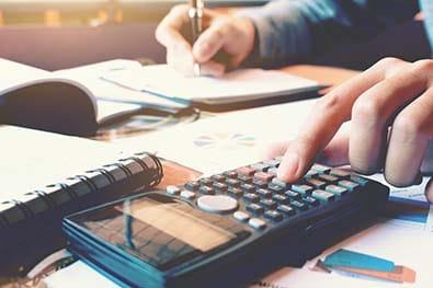 Main de femme tapant sur une calculatrice et écrivant des note sur un calepin