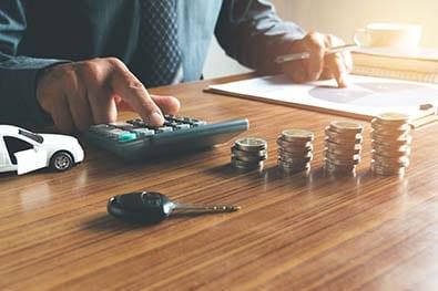 Homme d'affaire tapant sur sa calculette dans son bureau pour établir un budget sur un concept de voiture des pièces et des clés sur son bureau