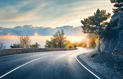 Route de montagne avec coucher de soleil et nuages