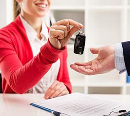 Une vendeuse donne les clés de voiture à son client