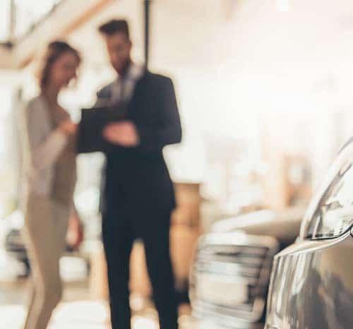 Deux personnes discutant en arrière plan d'une voiture