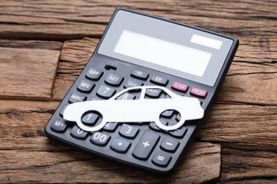 Voiture en papier posée sur une calculatrice